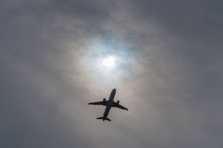 Airliner visible under a gash in the clouds