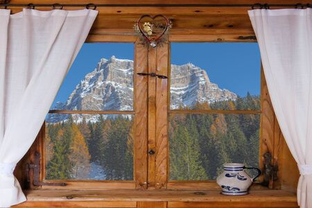 Window with Christmas decorations and in the background the snowy Pelmo mountain and fir and larch forest. Concept: Christmas cards with Dolomite landscapes 版權商用圖片
