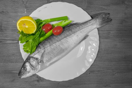 Color isolation effect of white dish with sea bass, lemon, celery and tomatoes on wooden background. Concept: cuisine based on fish