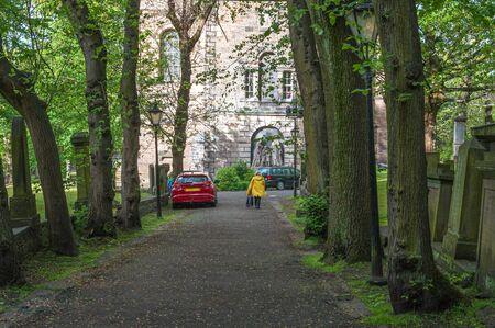 Unrecognizable person walking one tree lined street in Edinburgh