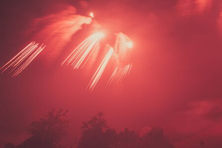 Bright red fireworks with wake effect over trees silhouette in the middle of fog, Vittorio Veneto, Italy