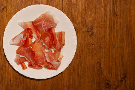 Top view of plate with speck slices on wooden background