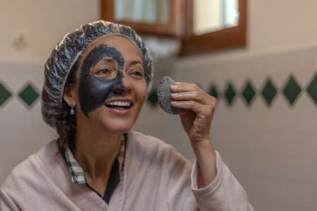 Close-up of a smiling woman while removing the mud mask from her face Imagens