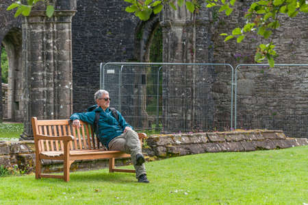 Man sitting on a bench in the ruins of the Inchmahome Priory, Menteith Lake, Scotland. Concept: relax in places with charm and mystery, travel to Scotland 免版税图像 - 157797570