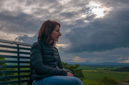 Girl sitting on a bench while contemplating thoughtfully the landscape in a cloudy day. Concept: relax in places with charm and mystery, travel to Scotland 免版税图像 - 157797575