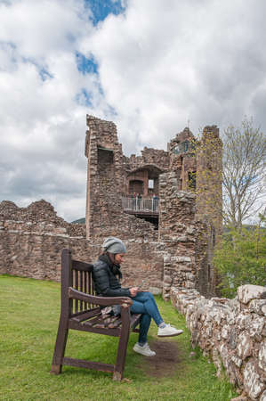 Girl sitting on a bench reading a book in the ruins of Urquhart Castle, Loch Ness, Scotland. Concept: relax in places with charm and mystery, travel to Scotland 免版税图像