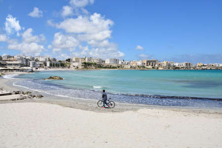 A lonely person on a bike on the beach of Otranto, an old town in the Puglia region, Italy. 版權商用圖片