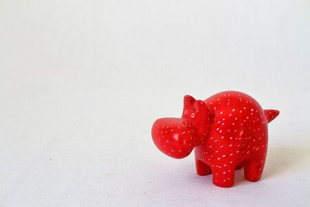 zoo animal: Toy hyppo carved wooden model, red and white spotted.