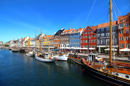 alte: Copenhagen, Denmark - June 5, 2016: Copenhagen, sunny view of Nyhavn harbor built in 17th-century flanked by antique colorful facades and old ships moored.