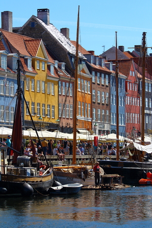 Copenhagen, Denmark - June 5, 2016: Copenhagen, sunny view of Nyhavn harbor built in 17th-century flanked by antique colorful facades and old ships moored.