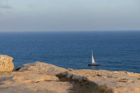 hobby hut: A panoramic view of the ocean with a blue sailboat at the bottom right.