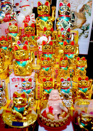 goodluck: Various lucky golden neko displayed on shelf with monk statue and ceramic neko and laughing buddha.