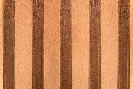 Old wallpaper with vertical brown and beige stripes  photo
