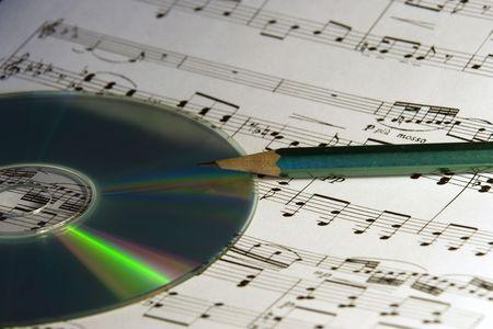 CD and dark - green pencil on musical notes sheet photo