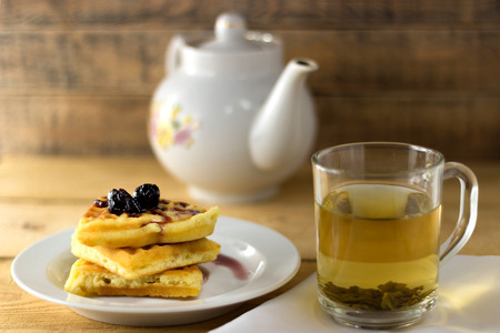Waffles with jam and green tea on a wooden background