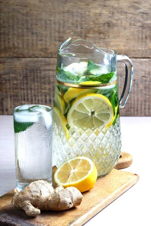 Fruit water with lemon, cucumber and mint in glass pitcher.