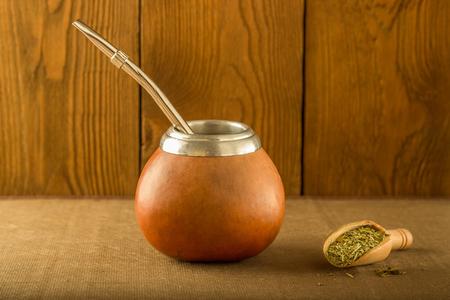yerba mate: Calabaza con yerba mate y una cuchara de madera contra el fondo de un árbol