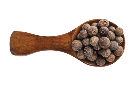 scattering: Wooden spoon with allspice seeds isolated on a white background