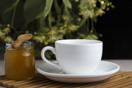 Tea in white with linden, honey jar and spoon on a bamboo stand