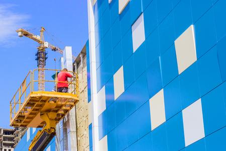 작업자가 집 외관에 직면 한 패널을 설치합니다.