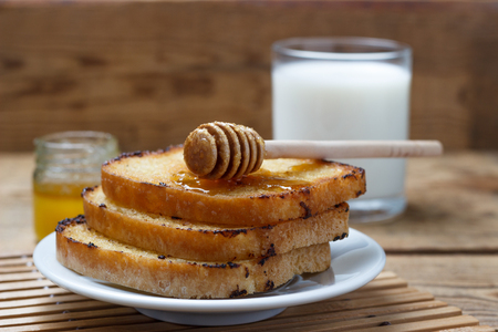 Fried toast on a white plate with milk and a can of honey on a wood background