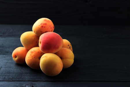Apricots on black wooden background