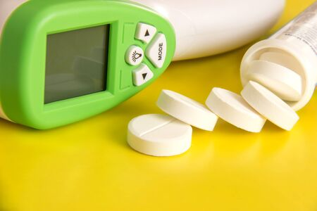 Round tablets and infrared thermometer on a yellow background