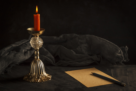 Still life, burning candle on a gadget and a sheet of old paper with a pencil