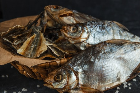 Basket of dried fish in craft paper on a dark background