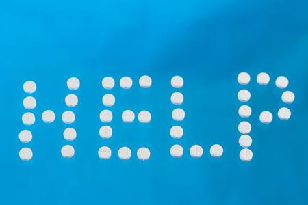 Inscription help laid out of white tablets on a blue Фото со стока