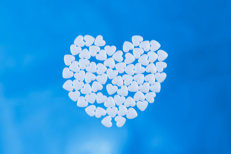 Heart laid out from tablets in the form of hearts on a blue