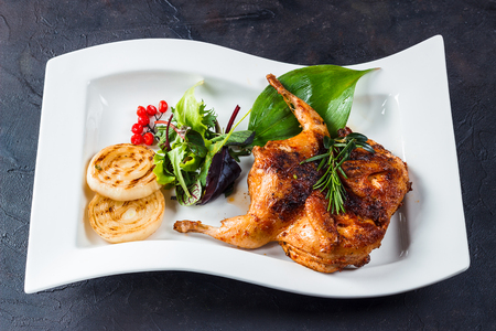 Grill quail tobacco on a white plate. With greens, onions and rasmarin