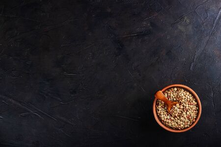 Lentils in a clay vessel and a wooden spoon with place for text on a black concrete
