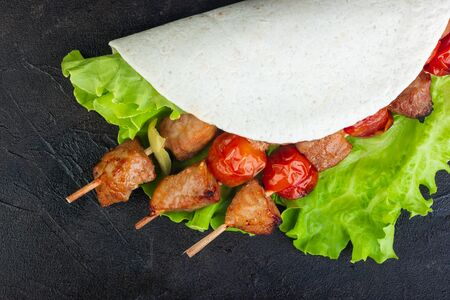 Pork on skewers with vegetables on lettuce and pita bread