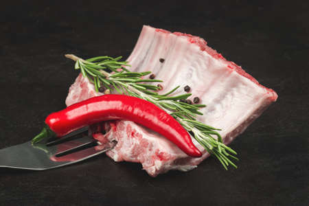 Raw pork ribs with rosemary and hot pepper on a barbecue fork
