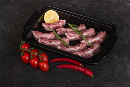 Raw pork ribs in a baking dish with lemon, hot pepper, tomatoes and rosemary