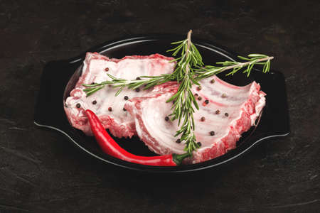 Raw pork ribs with rosemary and hot pepper in a baking dish