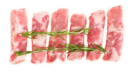 Sliced raw pork ribs with rosemary on a white plate, isolate