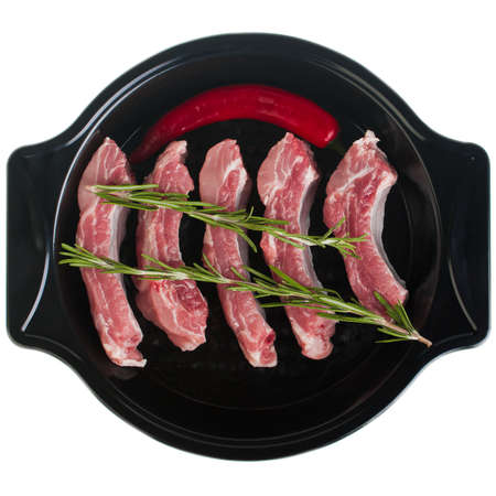 Pork ribs in a baking dish with rosemary and hot pepper, on a white plate, isolate