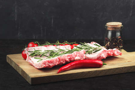 Raw pork ribs, with a branch of rosemary, garlic, hot pepper and tomatoes