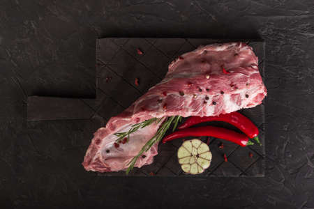 Raw pork ribs on a dark board with rosemary, hot pepper and a chock