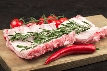 Raw pork ribs with rosemary branch, hot pepper and tomatoes Zdjęcie Seryjne