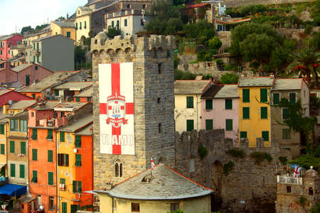 A glimpse of colorful buildings and the tower of Portovenere