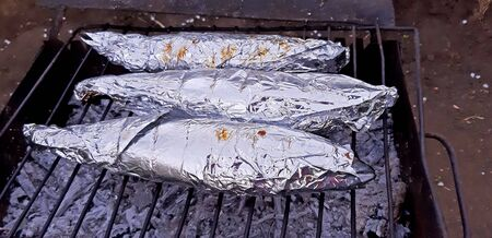 Grilled fish in the aluminum foil. Cooking process.