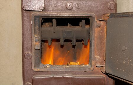 The fire burns in the stove winter home heating concept Banque d'images - 138071690