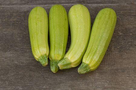 Zucchini benefits concept. Zucchini on wooden background.