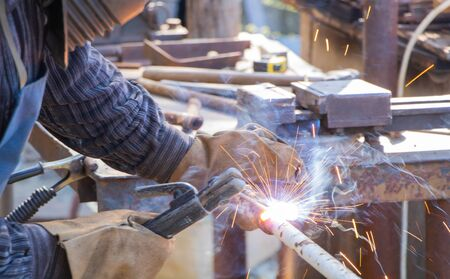 The worker welding metal pipe at the factory