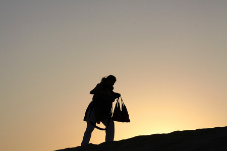 conveys: Single Woman walking uphill is silhoutted by the bright orange hues of the Dusk Twilight  Her posture perfectly conveys the peoples eternal struggles to overcome natures obstacles Editorial