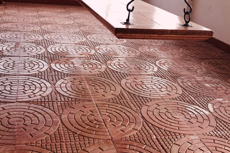 verandah: Intricately designed terracota tiles in a classic design are used on a verandah which has a flat wooden swing of polished teak wood