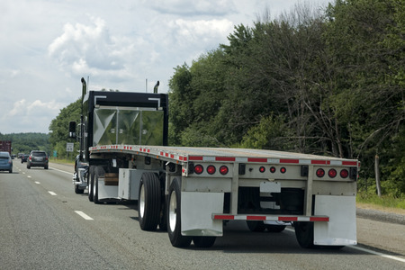 Rear view of empty flatbed trailer on highway.